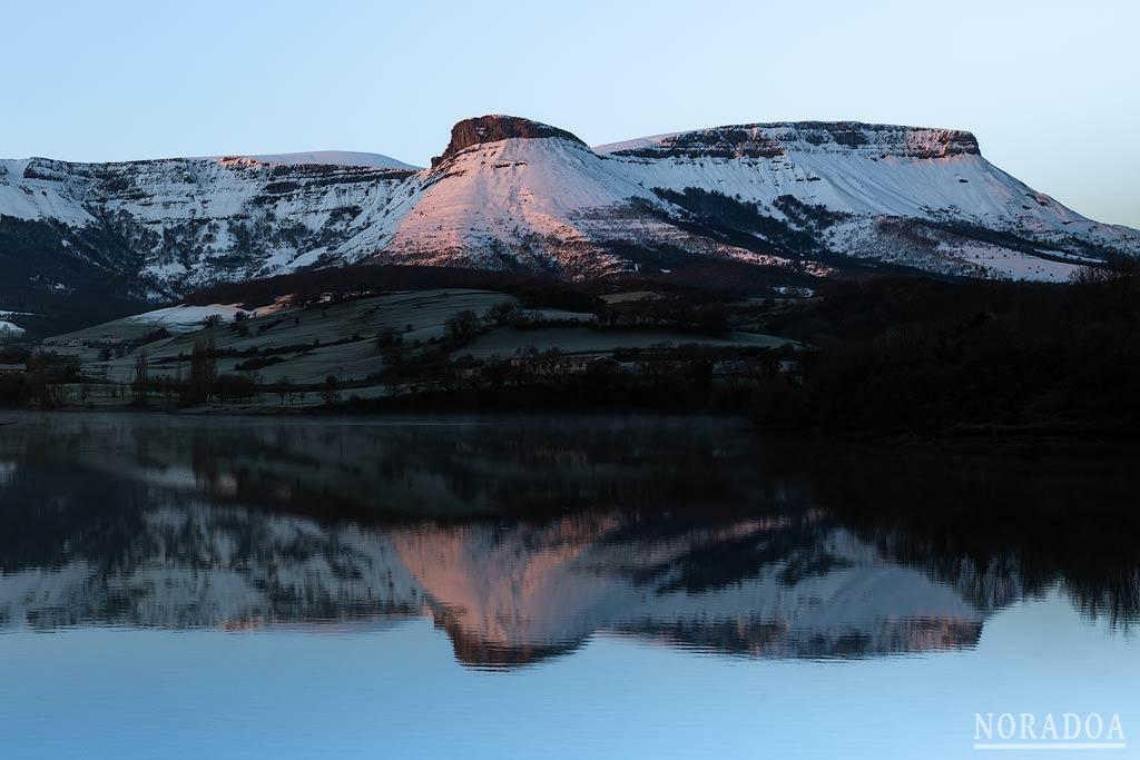 La sierra Salvada nevada reflejada en embalse de Maroño